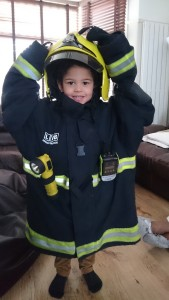 Tommy dressed up in his dad's firefighter uniform