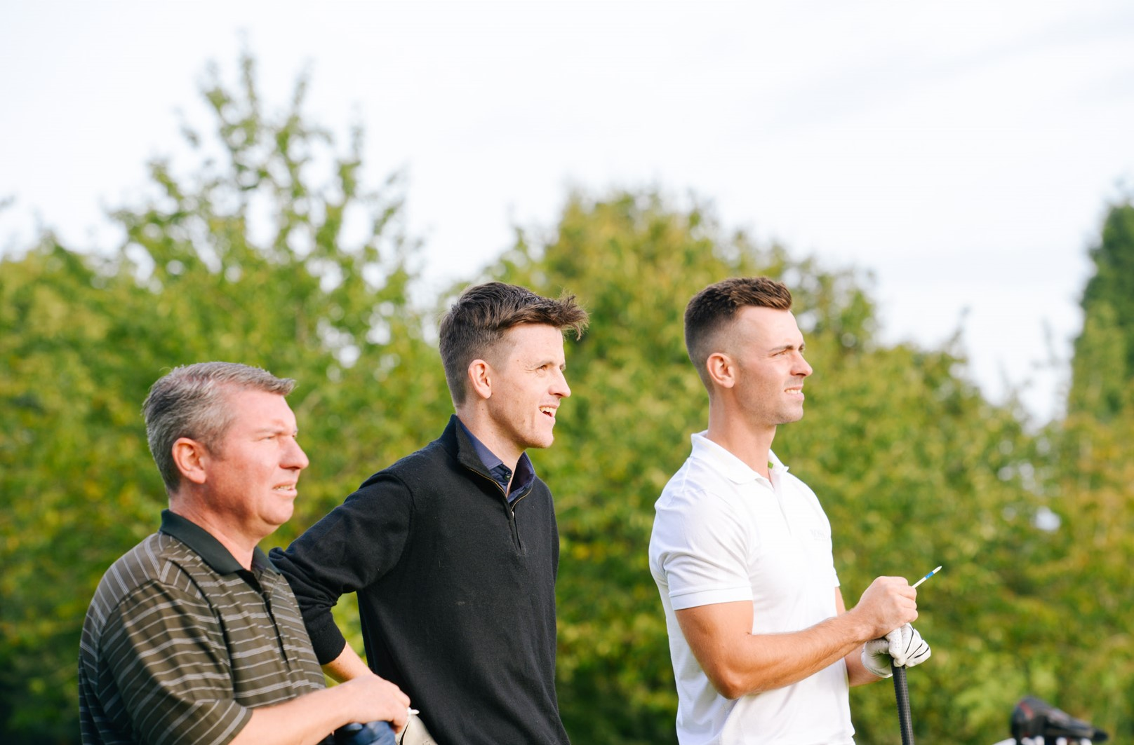 Three golf players assessing their game